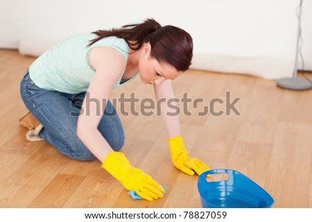 Gorgeous red-haired woman cleaning the floor while kneeling at home - stock photo