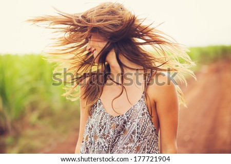 Gorgeous Romantic Girl Outdoors. Beautiful  Model in Short Dress in Field. Long Hair Blowing in the Wind. Backlit, Warm Color Tones - stock photo