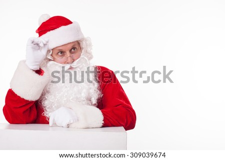 Gorgeous Santa Claus is standing and leaning on the white surface. He is looking aside seriously and touching his hat. Isolated on background and copy space in right side - stock photo