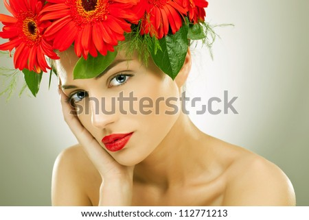 gorgeous seductive woman wearing flowers in her hair holding her head in her palm - vintage picture style
