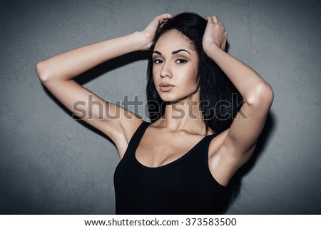 Gorgeous seductress. Beautiful young African woman in black swimsuit holding hands in hair and looking at camera while standing against grey background - stock photo