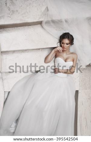 Gorgeous sexy bride in elegant dress posing on white stairs - stock photo