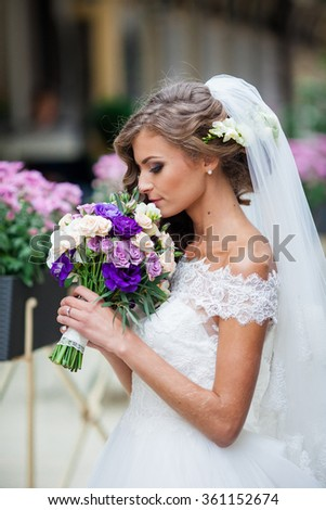 Gorgeous sexy bride in vintage dress smelling bouquet of flowers closeup - stock photo