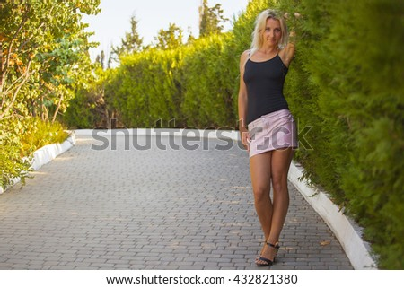 Gorgeous sexy tall slender blonde with a sexy face and a sports figure in a short skirt and light t-shirt stands on the Avenue in the Park next to the green flowered Bush in the city of Sevastopol