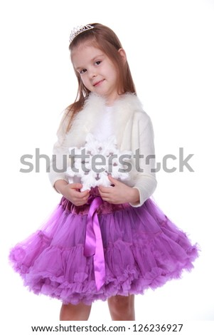Gorgeous smiley little girl holding huge white snowflake isolated on white on Holiday theme