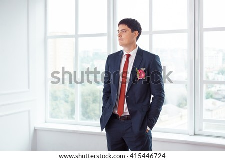 Gorgeous smiling groom. Handsome man in a suite with a buttonhole standing against a window indoors - stock photo