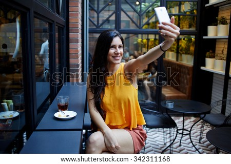 Gorgeous smiling Latin woman making self portrait with mobile phone camera while sitting in modern cafe inside, charming happy female posing while photographing herself for social network picture   - stock photo