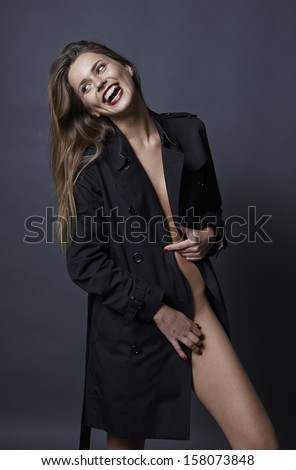 Gorgeous smiling long hair red lips woman in fashionable trench coat half naked in studio