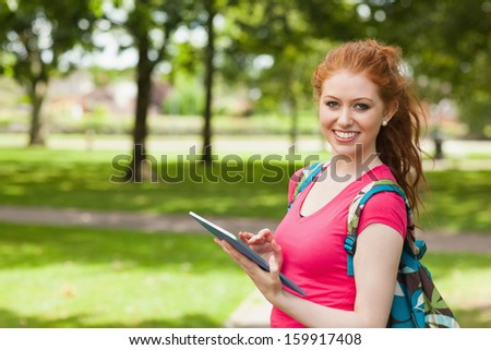 Gorgeous smiling student using tablet on campus at college - stock photo