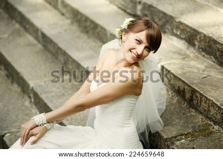 Gorgeous smiling young bride sitting on step.  - stock photo