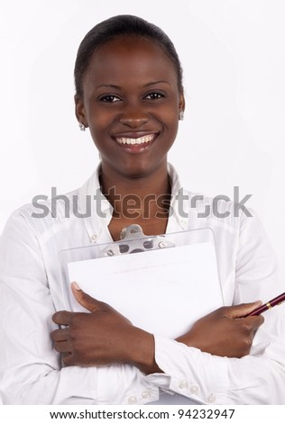 Gorgeous South African woman holding a notepad and pen to her chest, with a big smile. - stock photo