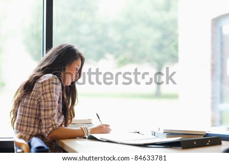 Gorgeous student working in a library - stock photo