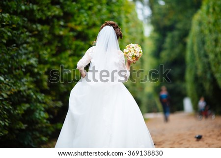 Gorgeous stylish blonde bride in vintage white dress walking in the park - stock photo
