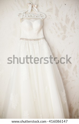 Gorgeous stylish white wedding dress on hanger on wall