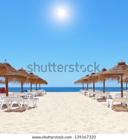 Gorgeous summer day at the beach near the sea. Beach umbrellas and sunbeds on the sand. - stock photo