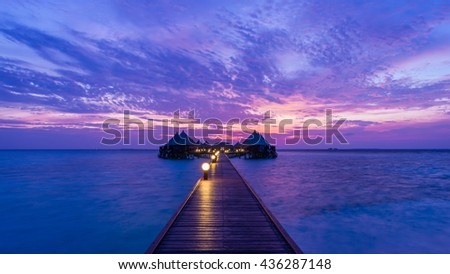 Gorgeous sunset over the ocean. Relaxing summer evening. Panorama of tropical island with over-water bungalows - stock photo