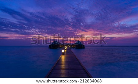 Gorgeous sunset over the ocean. Splash of waves on the white sand beach. Relaxing summer evening. Panorama of tropical island Beach with Over-water bungalows - stock photo