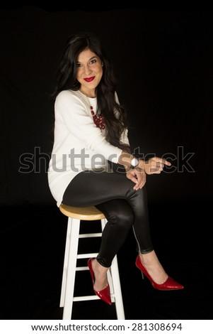 Gorgeous tan woman posing on bar stool - stock photo