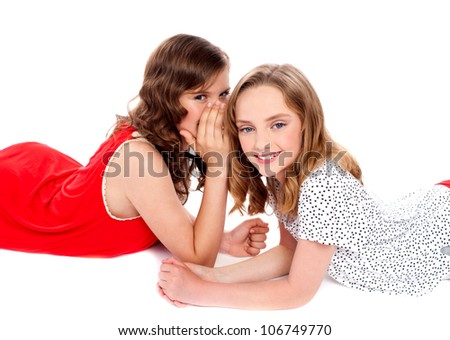 Gorgeous teenager laying on floor and sharing secret to each other - stock photo