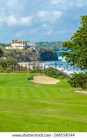 Gorgeous view at the beautiful golf course with sand bunkers at the ocean side. Vertical.