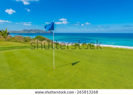 Gorgeous view at the golf course with blue flag at the ocean side. Gorgeous view at the golf course with blue flag at the ocean side. - stock photo