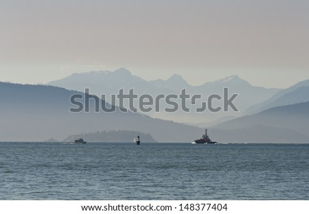 Gorgeous view at the marine scenery. A boat, ship, vessel moves across the ocean inlet  with the mountains and hills as a great background. Vancouver, Canada. - stock photo