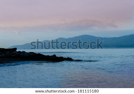 Gorgeous view at the marine scenery. Silhouette of the rocky beach dat the ocean inlet at sunset, sunrise time. Vancouver, Canada. - stock photo