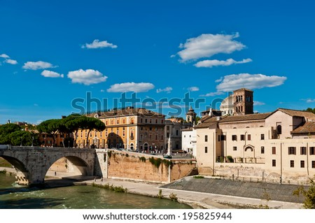 gorgeous view of Tiber Island and Pons Cestius bridge in Rome, Italy (against a gorgeous blue sky with clouds) - stock photo
