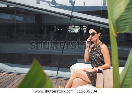 Gorgeous wealthy business woman dressed in elegant clothes speaking on her smart phone while enjoying rest after hard work day, modern female talking on her cellphone while siting near office building - stock photo