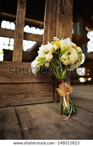 gorgeous wedding bouquet with a bow and heart  on a wooden surface
