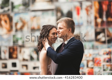 Gorgeous wedding couple, bride, groom kissing and hugging against the background of paintings