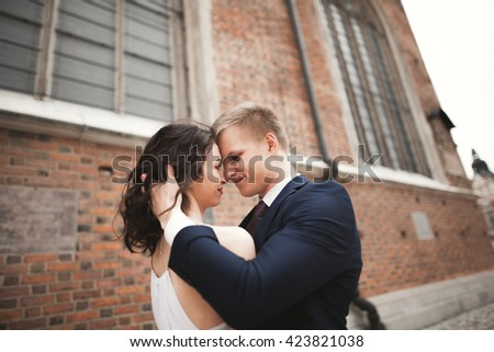 Gorgeous wedding couple, bride, groom posing near old gate building