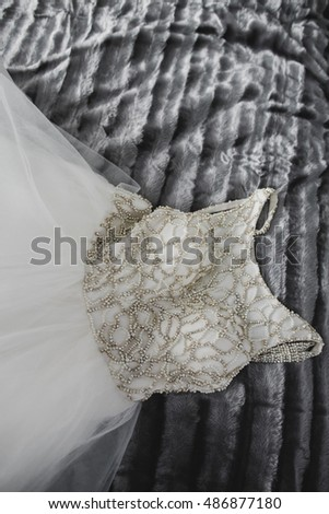 Gorgeous wedding gown with golden design lies over the grey blanket