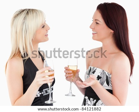 Gorgeous well-dressed women drinking champaign in a studio