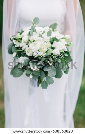 Gorgeous white wedding bouquet held by bride standing on green lawn