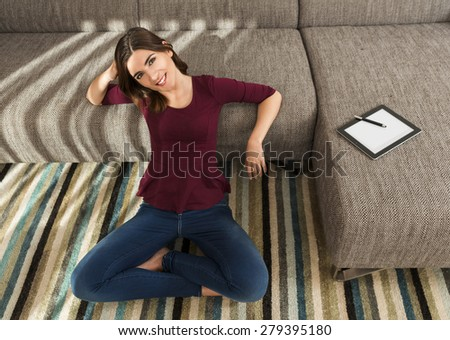 Gorgeous woman at home working with a tablet - stock photo