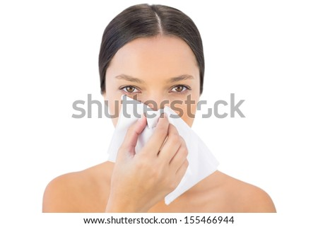 Gorgeous woman blowing her nose on white background