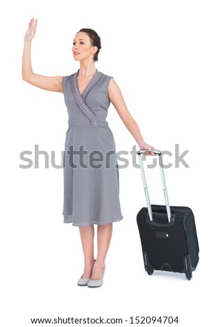 Gorgeous woman carrying her suitcase calling taxi on white background - stock photo