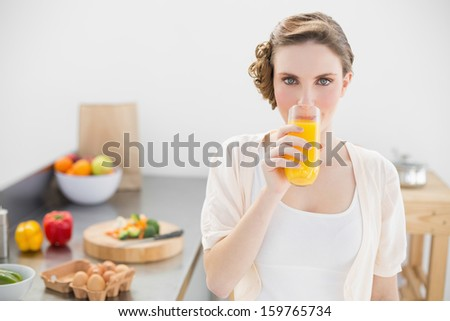 Gorgeous woman drinking a glass of orange juice standing in her kitchen looking at camera - stock photo