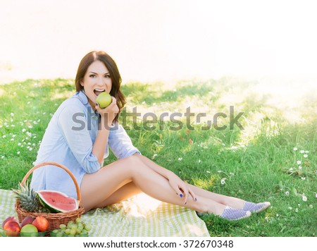 Gorgeous woman eating an apple in the park.