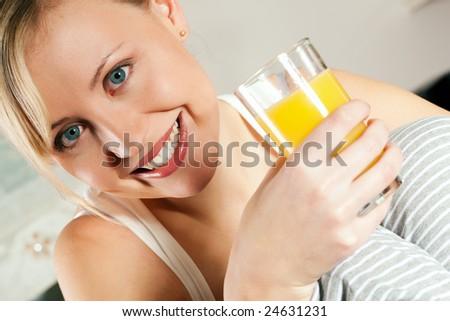 Gorgeous woman enjoying a glass of orange juice - stock photo
