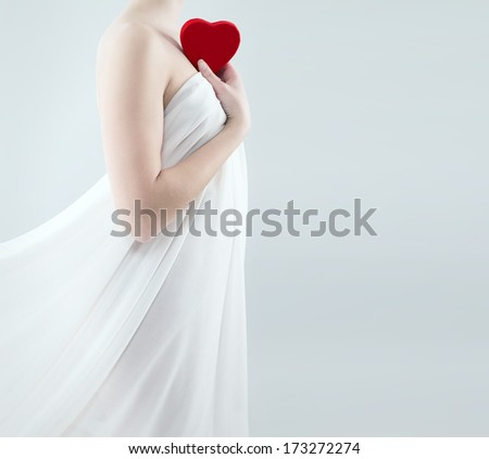 gorgeous woman in a white drape holding red heart to her shoulder - stock photo