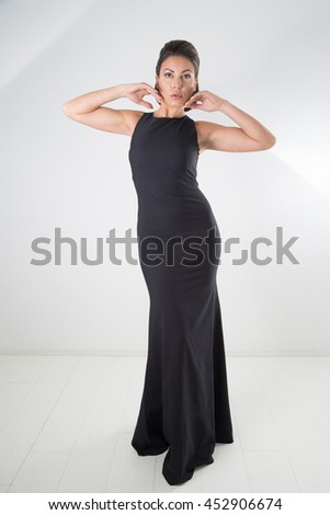 Gorgeous Woman In Black Evening Gown With Classic Hairstyle And Makeup Posing With Raised Arms, Full-Length Studio Shot Over White Background - stock photo