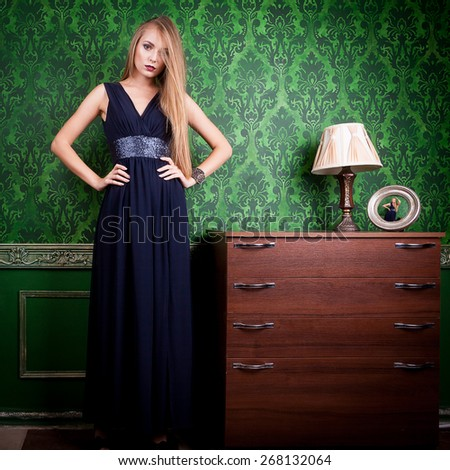 Gorgeous woman in long blue dress on green vintage background with a lamp on a desk. Beauty and fashion. Retro old styled image. Sensuality. Fashion - stock photo