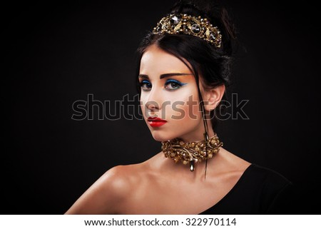 Gorgeous woman in luxury jewelry against black background - stock photo