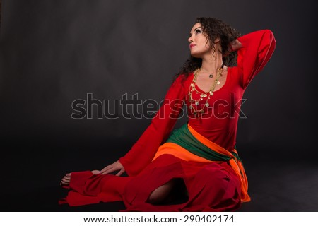 Gorgeous woman in red on a black background. Portrait of sexual, emotional girl. Gypsy. Actress dressed like a gypsy. Subject Theatre, Art.