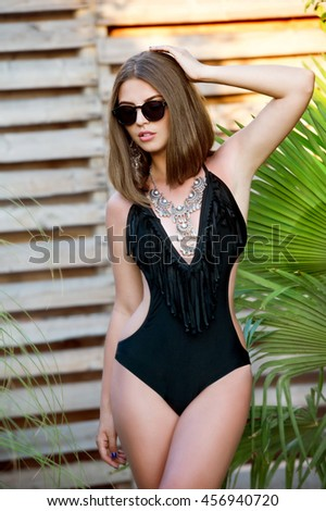 Gorgeous woman in sunglasses and elegant bikini relaxing on jungle - stock photo