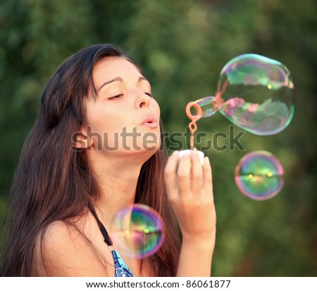 Gorgeous woman inflating soap-bubbles