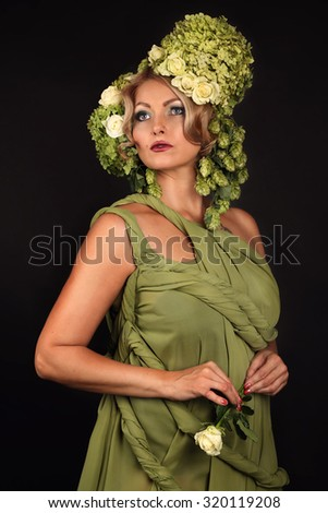 Gorgeous woman portrait with wreath from green flowers on head and with rose in hand over black background. Beauty Woman Face. Vogue Styled Fashion Portrait. Professional makeup. - stock photo