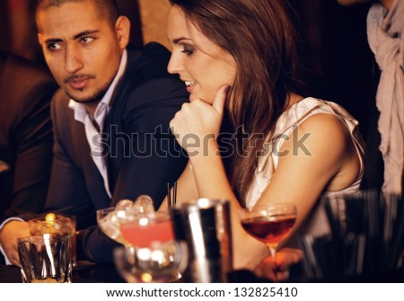 Gorgeous woman sitting at the bar with her handsome boyfriend - stock photo